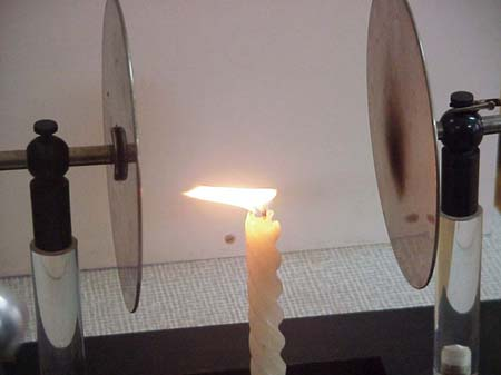 Because the flame has a bunch of free charged particles it is pushed and pulled by