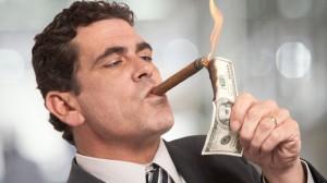 Rich-Businessman-Lighting-Cigar-With-100